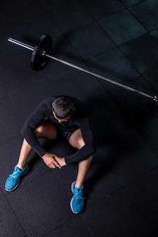 Bebaarde man trainen in de sportschool fitness breken ontspannen na het trainen van sport met halter.
