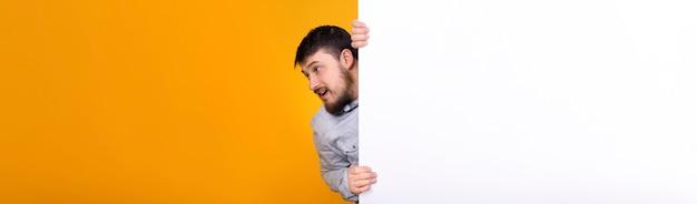 Bebaarde man trekt banner met plaats voor tekst, conceptruimte voor uw advertentie, panoramisch beeld