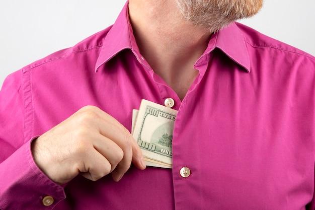Bebaarde man trekt geld in een shirt