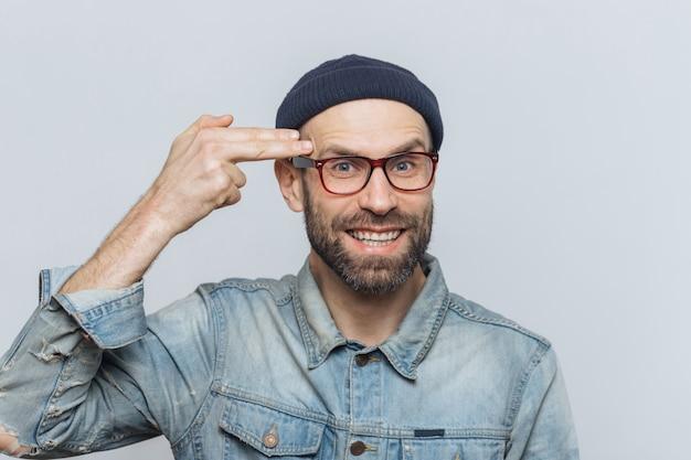 Bebaarde man van middelbare leeftijd met blauwe ogen heeft plezier, dwaas en maakt zelfmoordgebaar
