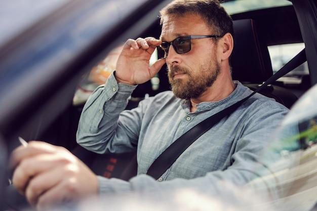 Bebaarde man van middelbare leeftijd met een bril die zijn auto bestuurt