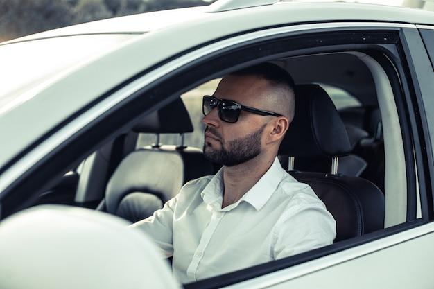 Bebaarde man van stijl en status. knappe jonge man in volledig pak glimlachend tijdens het besturen van een witte auto.