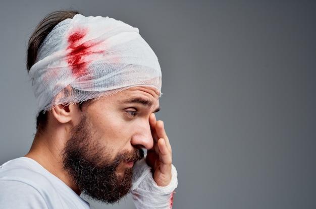 Bebaarde man verbonden hoofd en hand bloed geïsoleerde achtergrond