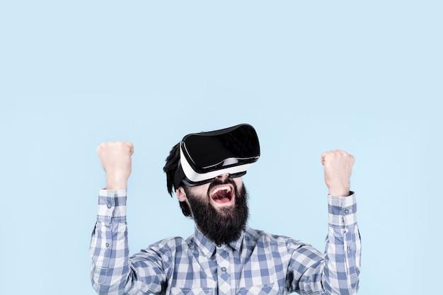 Bebaarde man verheugt zich over overwinning in virtual reality-bril (vr-bril)