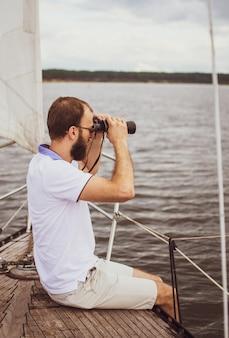 Bebaarde man verrekijker kijken op de zeilboot