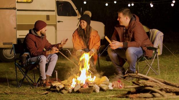 Bebaarde man vertelt een grappige grap aan zijn vrienden rond het kampvuur. retro camper. kampeer tent.