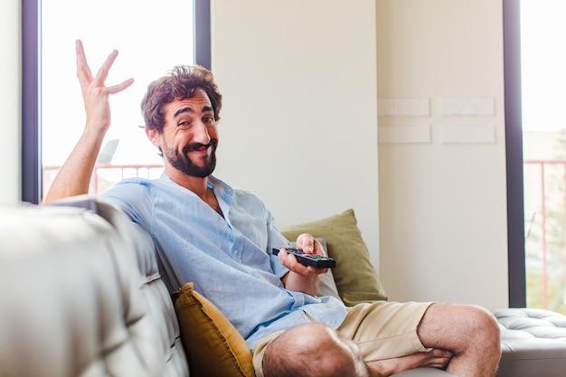 Bebaarde man voelt zich gelukkig, verrast en opgewekt, lacht met een positieve houding, realiseert zich een oplossing of idee