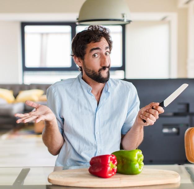 Bebaarde man voelt zich verbaasd en verward, twijfelt, weegt of kiest verschillende opties met een grappige uitdrukking