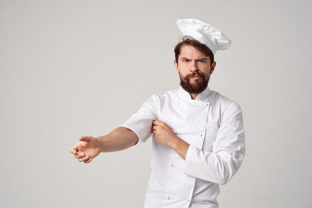 Bebaarde man werk uniform beroep keuken lichte achtergrond. hoge kwaliteit foto