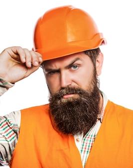 Bebaarde man werknemer met baard bij het bouwen van helm of harde hoed.