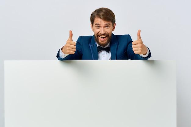 Bebaarde man witte banner in de hand blanco blad presentatie copyspace studio