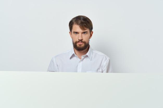 Bebaarde man witte banner in de hand blanco vel presentatie witte achtergrond. hoge kwaliteit foto