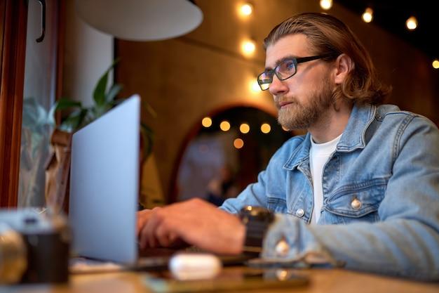 Bebaarde man zit aan cafétafel met laptop, freelancer werkt graag op afstand