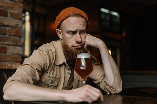 Bebaarde man zit alleen, bier drinken in pub