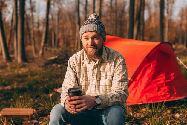 Bebaarde man zit in de buurt van de camping tent. jonge wandelaar man genieten van de lucht in het bos