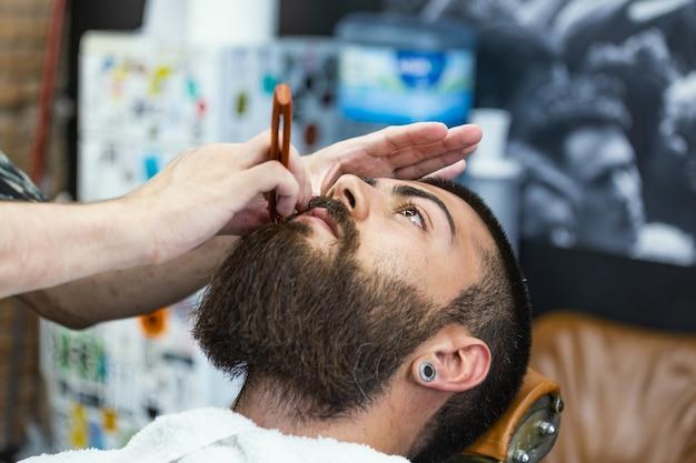 Bebaarde man zit in een fauteuil in een kapper terwijl kapper zijn baard struikelt met een schaar