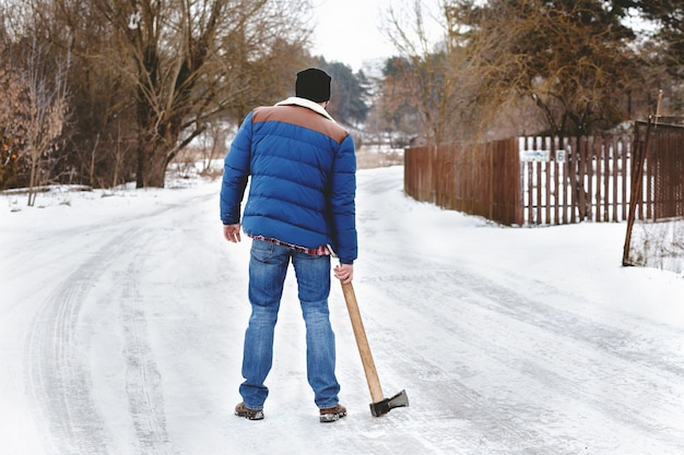 Bebaarde maniak met een bijl die op een sneeuwweg loopt