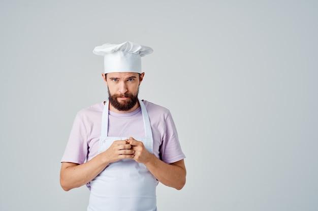 Bebaarde mannelijke chef-kok in restaurants met witte schort keukengerei