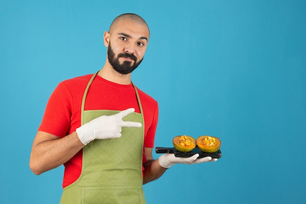 Bebaarde mannelijke chef-kok in schort en handschoenen met een donkere houten plank met gebak.