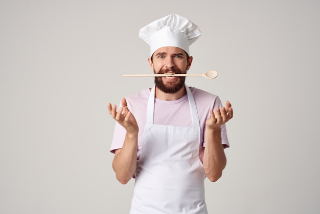 Bebaarde mannelijke chef-kok in uniforme lepel in tanden die in een restaurant werken
