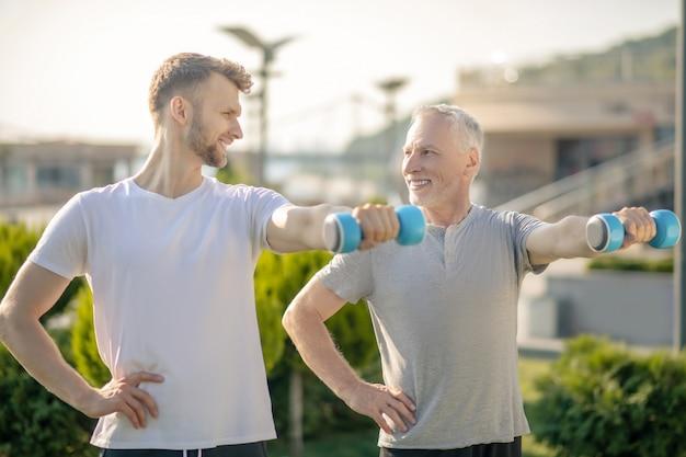 Bebaarde mannelijke en volwassen man met blauwe halters, oefenen
