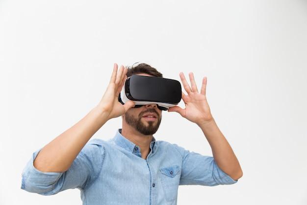 Bebaarde mannelijke gebruiker in vr-bril die van ervaring geniet