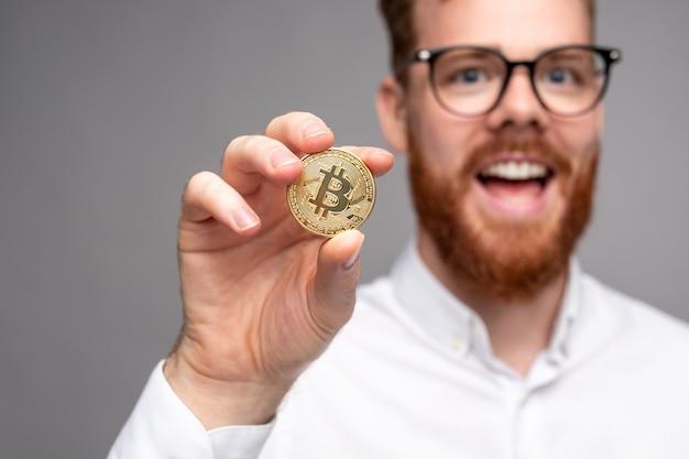 Bebaarde mannelijke investeerder die bitcoin toont
