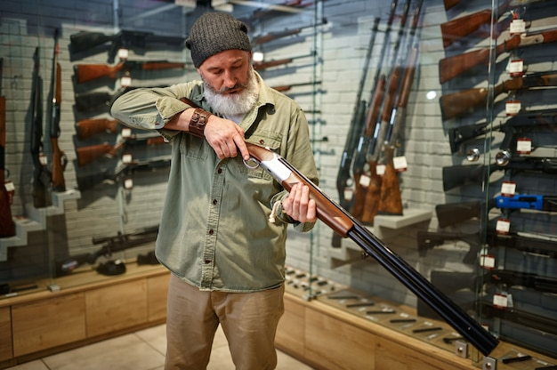 Bebaarde mannelijke jager laadt jachtgeweer in wapenwinkel. wapenwinkelinterieur, munitie- en munitie-assortiment, vuurwapenkeuze, schiethobby en lifestyle