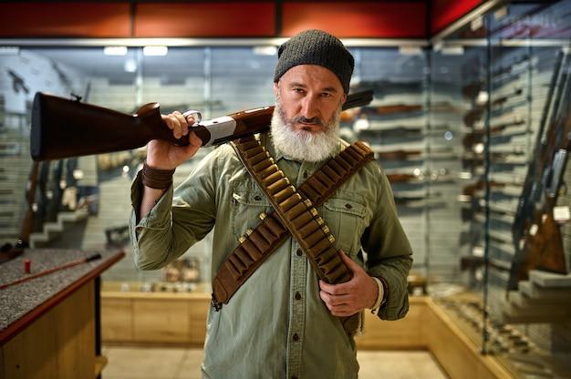 Bebaarde mannelijke jager met geweer en bandeliers in wapenwinkel. wapenwinkelinterieur, munitie- en munitie-assortiment, vuurwapenkeuze, schiethobby en lifestyle