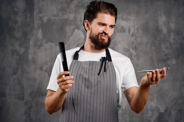 Bebaarde mannelijke kapper in schort kam schaar service