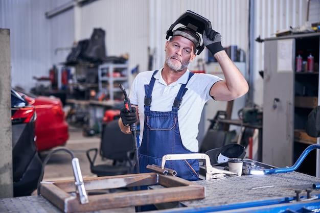Bebaarde mannelijke werknemer die lashelm opstijgt en naar de camera kijkt met een serieuze uitdrukking terwijl hij een laspistool vasthoudt