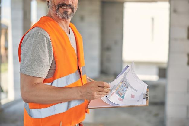Bebaarde mannelijke werknemer met een klembord met blauwdrukken in zijn handen