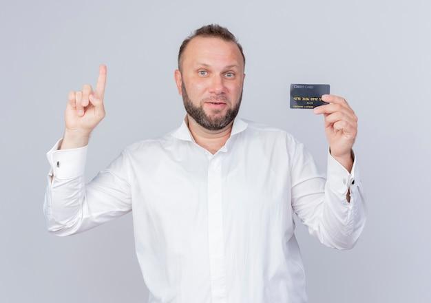 Bebaarde mens die wit overhemd draagt dat creditcard toont die wijsvinger toont die met gelukkig gezicht glimlacht met nieuw idee dat zich over witte muur bevindt