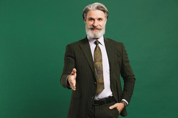 Bebaarde mens op middelbare leeftijd in de groeten van de kostuumhand op groene muur