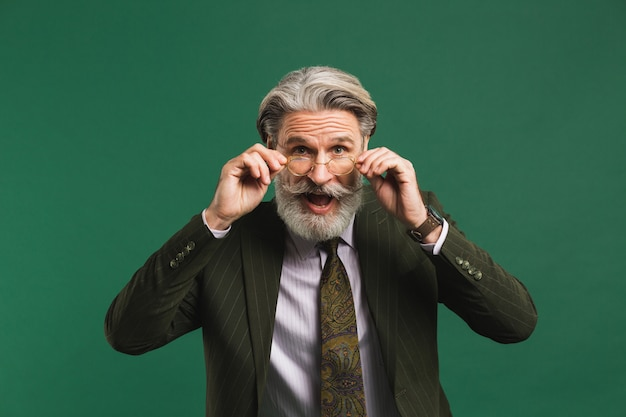 Bebaarde middelbare leeftijd leraar in pak houdt een bril met zijn handen en knippert zijn ogen met plezier op groene muur