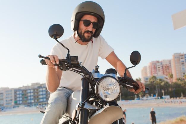 Bebaarde motorrijder buitenshuis.