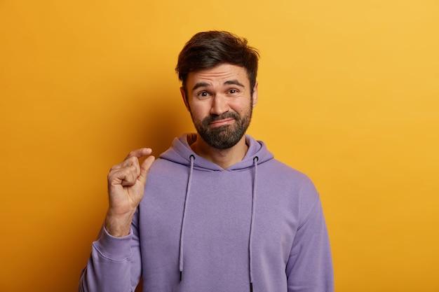 Bebaarde niet onder de indruk man toont een klein gebaar, toont een kleine hoeveelheid van iets, vormt een klein voorwerp, zegt dat dat alles is wat ik nodig heb, gekleed in een casual sweatshirt, geïsoleerd op een gele muur