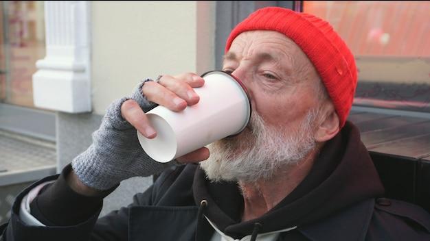 Bebaarde oude man, dakloze man die een warm drankje drinkt om warm te blijven. een vermoeide dakloze man drinkt thee zittend op een karton op straat