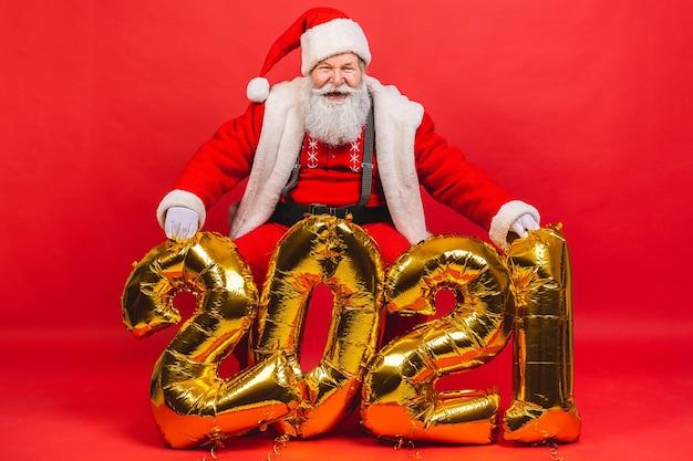 Bebaarde oude man in santa claus-kostuum dichtbij gouden baloons van 2021 die op rode achtergrond worden geïsoleerd