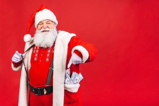 Bebaarde oude man in santa kostuum met geld in zijn zak geïsoleerd op een rode achtergrond