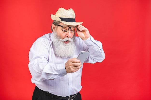 Bebaarde oude man met hoed en mobiele telefoon geïsoleerd op rode achtergrond