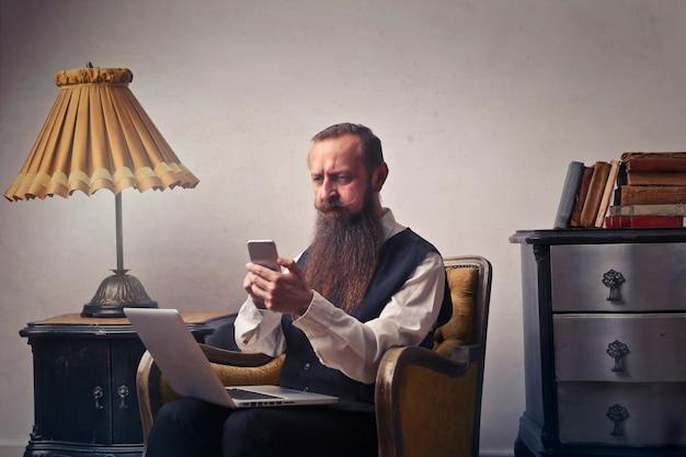 Bebaarde ouderwetse man met smartphone en laptop