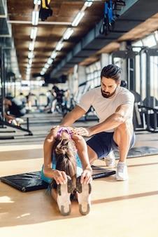 Bebaarde persoonlijke trainer die vrouw helpt uit te rekken. vrouw zittend op de mat.