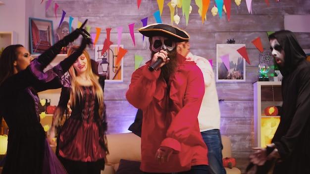 Bebaarde piraat die karaoke zingt op halloween-feest. groep vrienden in kostuums dansen en hebben plezier op de achtergrond