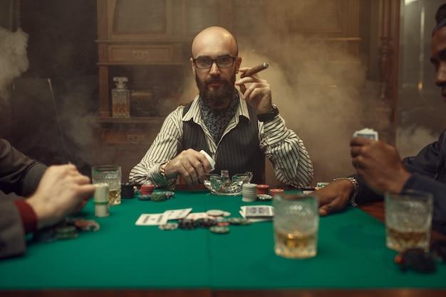 Bebaarde pokerspeler met sigaar, casino. verslaving. man ontspant in gokhuis