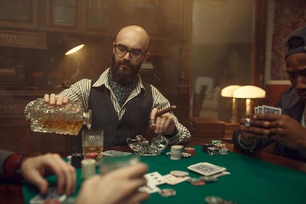 Bebaarde pokerspeler met sigaar giet whisky, casino. verslaving. man ontspant in gokhuis