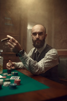Bebaarde pokerspeler met sigaar spelen in casino. verslaving
