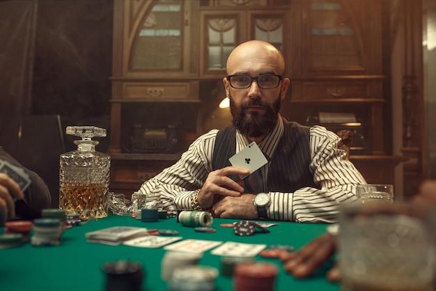Bebaarde pokerspeler toont aaskaart, casino. verslaving