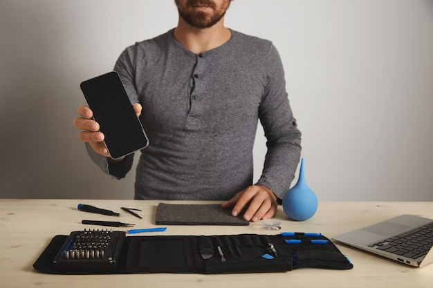 Bebaarde professional toont gerepareerde vaste smartphone na vervanging van de dienst, boven zijn specifieke tools in toolkit-tas in de buurt van laptop op houten witte tafel