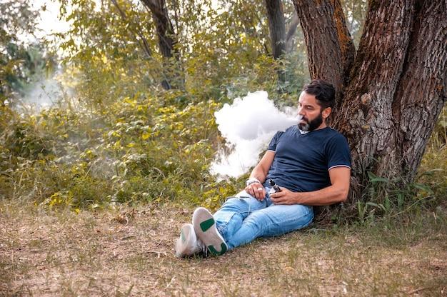 Bebaarde roker blaast een stel een e-sigaret op in de natuur